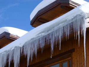 view of snow and frozen icicles on roof top
